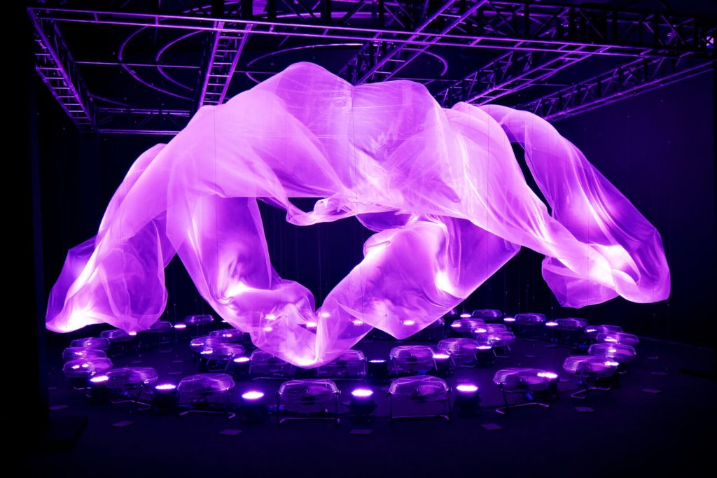 purple fabric suspended in air and manipulated by fans